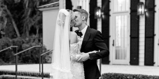 a person standing in front of a building: Finally, the first look at Hailey Baldwin's dress for her wedding to Justin Bieber is here. Baldwin chose a long, elegant white dress for the evening ceremony.