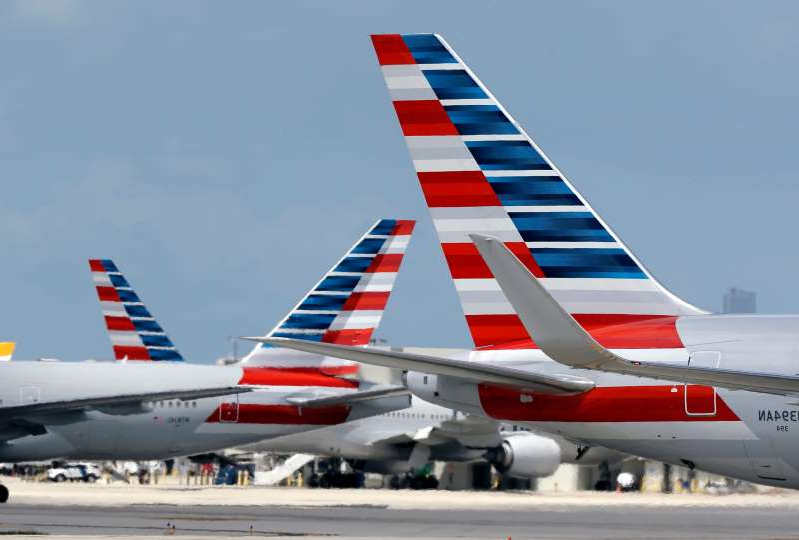 a red and white plane sitting on top of a runway: American Airlines jets taxi at Miami International Airport, in Miami.