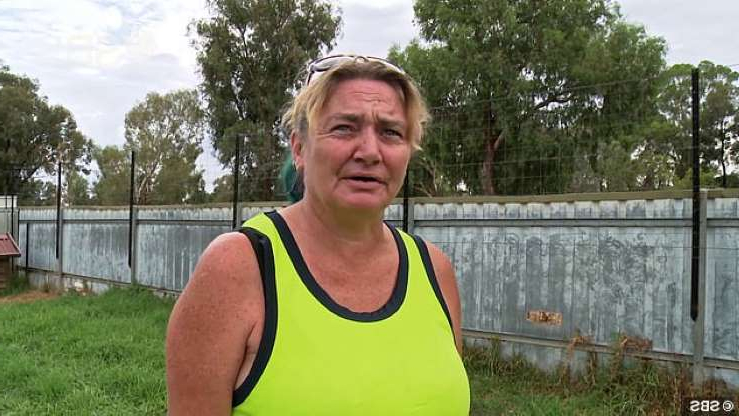 a woman posing in front of a fence: Kristi (pictured) and her partner are trying to raise their daughter in a safe and loving home in Wagga Wagga