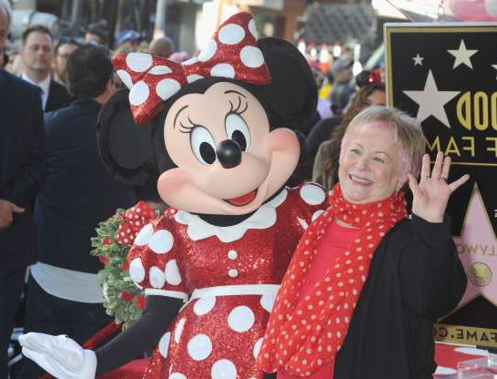 Slide 31 of 172: HOLLYWOOD, CA - JANUARY 22:  Voice actress Russi Taylor, who has voiced Minnie Mouse since 1986, poses with Minnie Mouse during a star ceremony in celebration of the 90th anniversary of Disney's Minnie Mouse at the Hollywood Walk of Fame on January 22, 2018 in Hollywood, California.  (Photo by Albert L. Ortega/Getty Images)