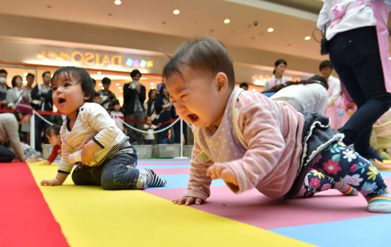a group of people sitting at a table: Japan is struggling with one of the world's lowest birth rates