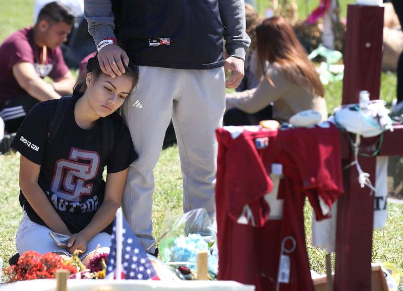 a group of people standing around a table: Gabriel Constantino and Nikki Healey, from Marjory Stoneman Douglas High School, stand together at a memorial after walking out of school to honor the memories of 17 classmates and teachers that were killed during a mass shooting at the school on March 14, 2018 in Parkland, Florida.