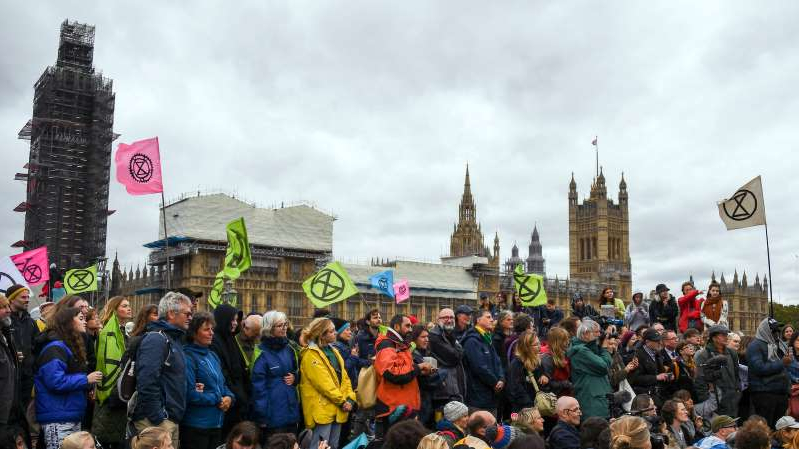 a group of people standing in front of a crowd posing for the camera: Climate activists gathered on Westminster Bridge, next to Britain's Parliament, during an Extinction Rebellion protest in London on Monday.