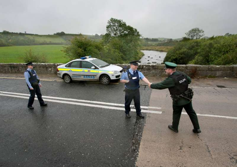 a group of people walking through a parking lot: A file photograph from 2011 of interaction between the PSNI and gardai on the border. Photo: Mark Condren