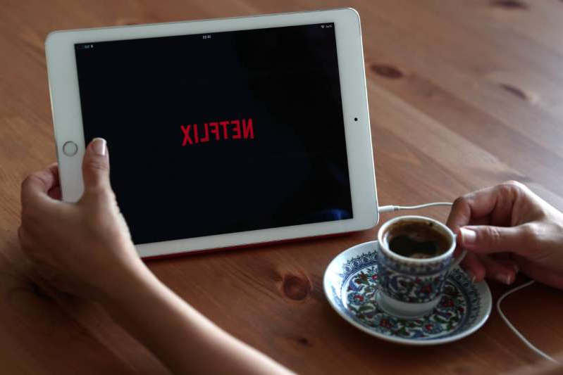a hand holding a cup of coffee: netflix