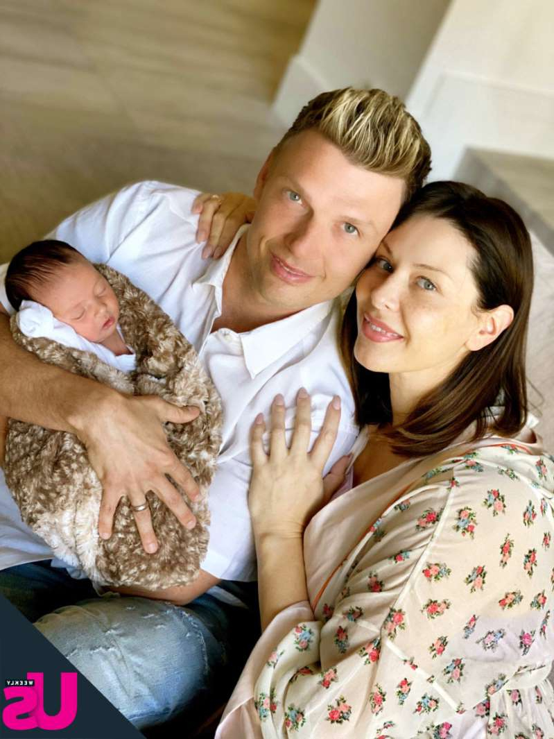 a man and a woman sitting on a bed: Nick Carter, Lauren Kitt, and Saoirse Reign Carter