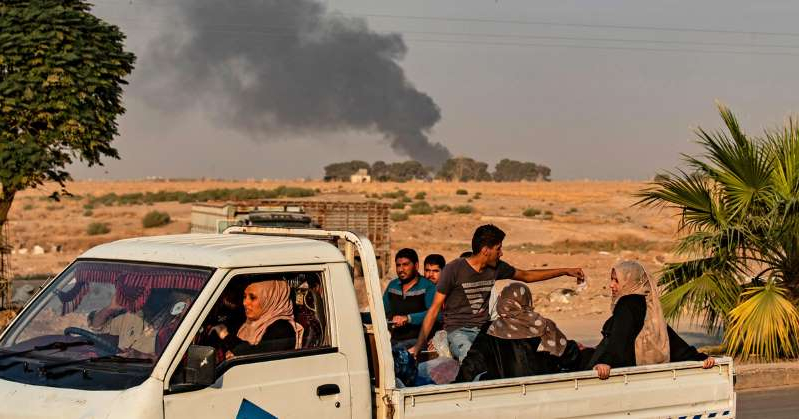 a man driving a car: Civilians ride a pickup truck as smoke billows following Turkish bombardment on the Syrian town of Ras al-Ain along the Turkish border on October 9, 2019. Delil Souleiman/AFP via Getty Images