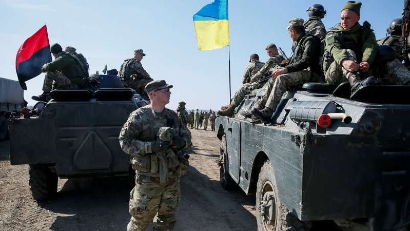 a man in a military vehicle: An American military instructor with Ukrainian servicemen during a multinational security training in Lviv, Ukraine last month. The State Department did not publicly announce $141 million in military assistance to Ukraine.