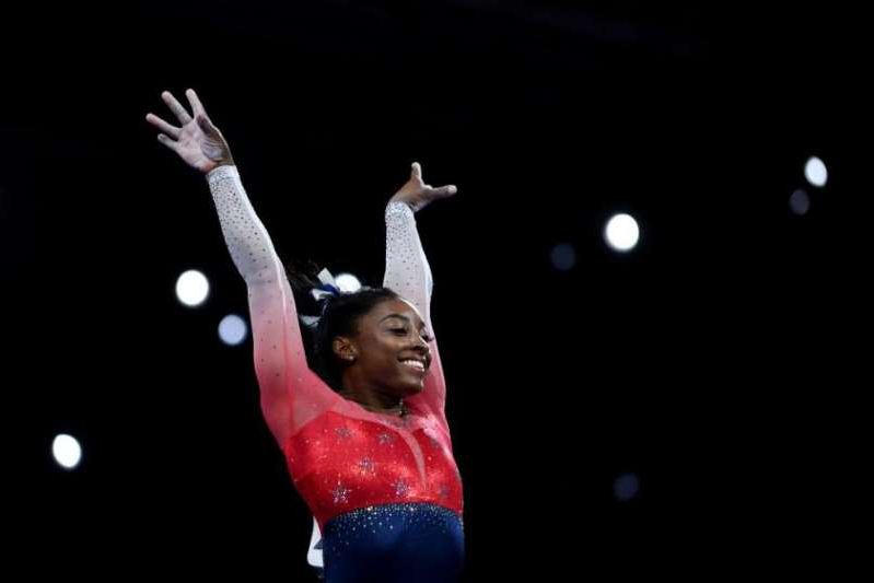 a man jumping in the air: Simone Biles.