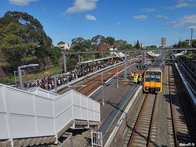 a train on a steel track: Commuters have been told to prepare for significant delays on train lines across Sydney after a person died at Erskineville train station