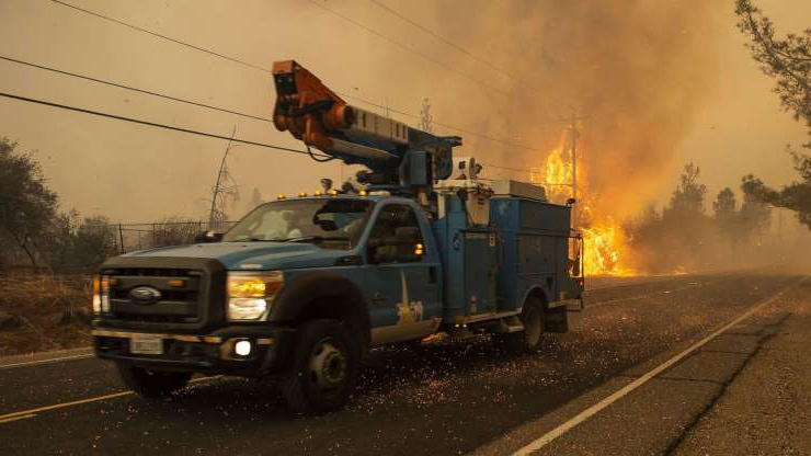 a truck that is driving down the road: A PG&E truck makes its way past a hot spot Pentz Rd. during the Camp Fire in Paradise, Calif., on Nov. 8, 2018.