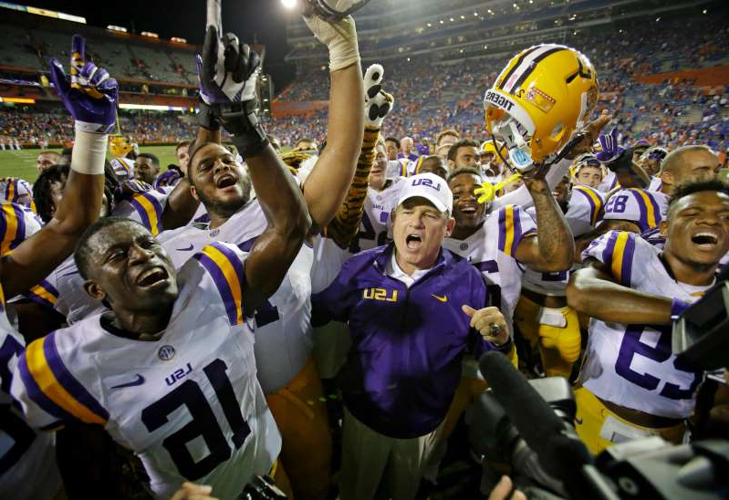 Les Miles et al. in uniform: LSU coach Les Miles, center, celebrates with players including safety Rickey Jefferson (29) and defensive back Tre'Davious White (16) after Saturday's thrilling win Saturday.
