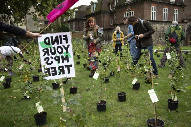 Slide 12 of 52: Extinction Rebellion climate change activists bring in small trees and invite MPs to come an collect one tree each as sites around Westminster are blocked on 8th October 2019 in London, England, United Kingdom.