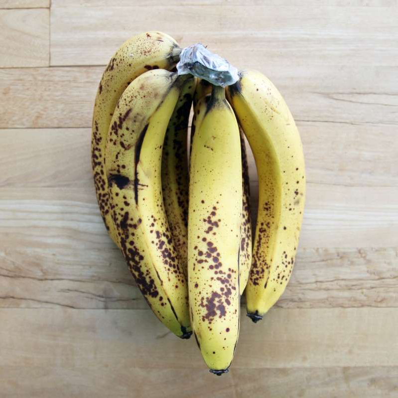 a banana sitting on top of a wooden table: The Smartest Way to Freeze Bananas For Smoothies, Banana Bread, and More