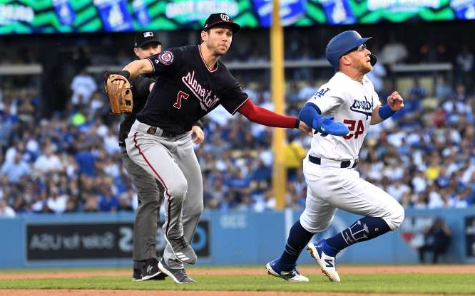 a baseball player pitching a ball on a field: Los Angeles Dodgers baserunner Matt Beaty, left, is tagged out by Washington Nationals shortstop Tre Turner before reaching second base on a double play in the second inning during Game 5 of the National League Division Series at Dodger Stadium in Los Angeles on Wednesday, Oct. 9, 2019.