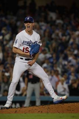 a baseball player pitching a ball on a field: Los Angeles Dodgers pitcher Walker Buehler yells out after striking out the Washington Nationals' Ryan Zimmerman to end the sixth inning during Game 5 of the National League Division Series at Dodger Stadium in Los Angeles on Wednesday, Oct. 9, 2019.