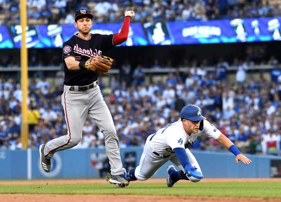 a baseball player swinging a bat at a baseball game: Los Angeles Dodgers baserunner Matt Beaty, left, is tagged out by Washington Nationals shortstop Tre Turner before reaching second base on a double play in the second inning during Game 5 of the National League Division Series at Dodger Stadium in Los Angeles on Wednesday, Oct. 9, 2019.
