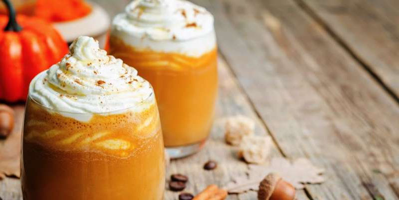 a close up of a glass cup on a wooden table: A homemade pumpkin spice latte recipe that is healthier, tastier and quicker than Starbucks.