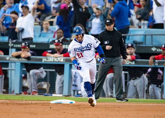 a crowd of people watching a baseball game: The Los Angeles Dodgers' Max Muncy (13) reacts as he runs the bases after hitting a two-run home run in the first inning against the Washington Nationals during Game 5 of the National League Division Series at Dodger Stadium in Los Angeles on Wednesday, Oct. 9, 2019.