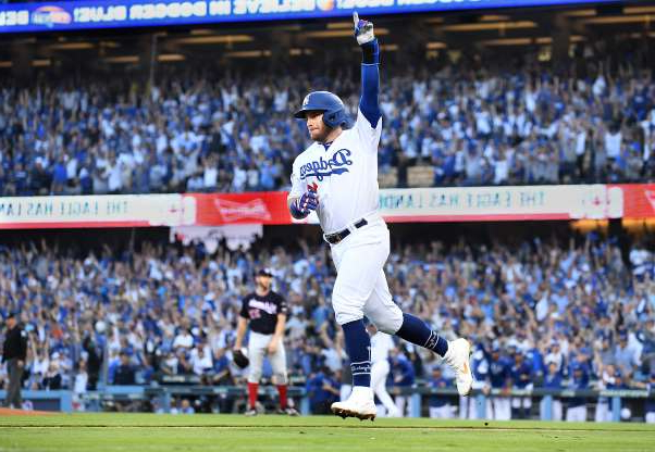 a crowd of people watching a baseball game: The Los Angeles Dodgers' Max Muncy celebrates his two-run home against the Washington Nationals in the first inning during Game 5 of the National League Division Series at Dodger Stadium in Los Angeles on Wednesday, Oct. 9, 2019.