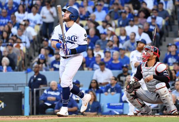a crowd of people watching a baseball game: The Los Angeles Dodgers' Max Muncy watches the flight of his two-run home against the Washington Nationals in the first inning during Game 5 of the National League Division Series at Dodger Stadium in Los Angeles on Wednesday, Oct. 9, 2019.