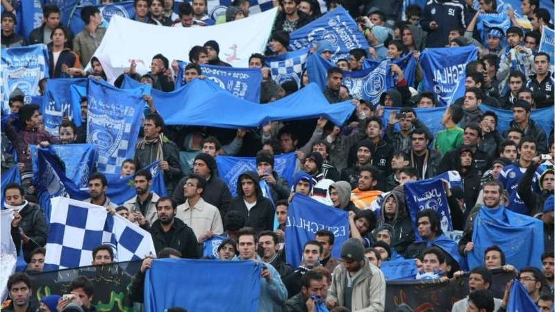 a group of people in front of a crowd: Iranian female soccer fan 'blue girl' dies after setting herself on fire. She was being charged with being dressed as a man to watch a soccer game. Women are not allowed to enter the soccer stadium in Iran.