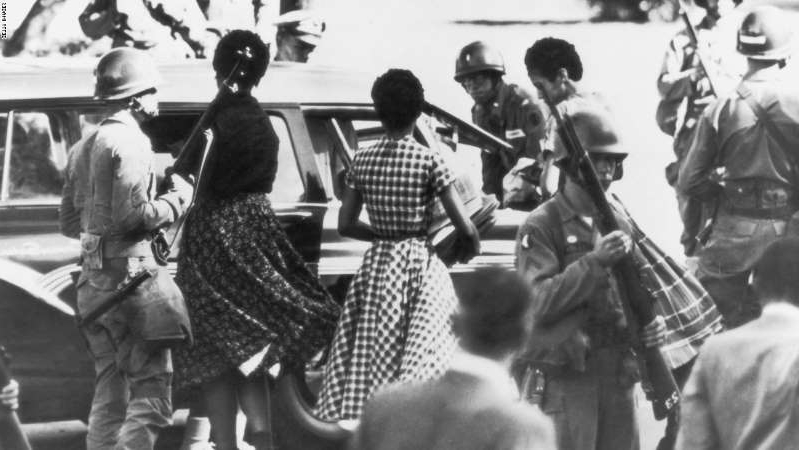 a group of people in uniform: Black students are provided with a military escort when entering and leaving Little Rock Central High School, Arkansas, following the school's desegregation in 1957.