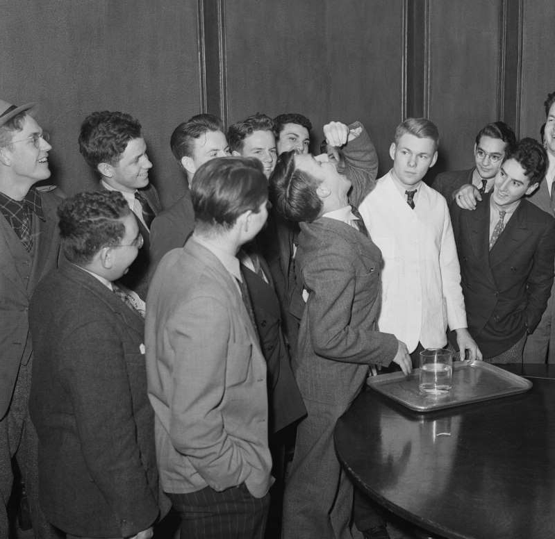 a group of people posing for a photo: Harvard freshman Lothrop Withington, Jr., swallows a live goldfish in 1939, winning $10 in a bet.