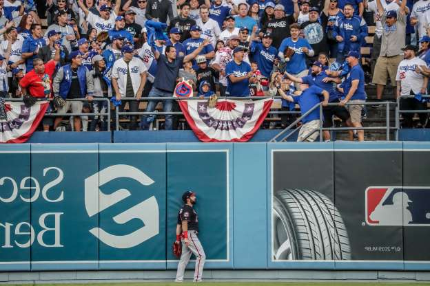 a group of people standing in front of a crowd: Washington Nationals right fielder Adam Eaton can't reach a solo home run by the Los Angeles Dodgers Enrique Hernandez in the second inning during Game 5 of the National League Division Series at Dodger Stadium in Los Angeles on Wednesday, Oct. 9, 2019.