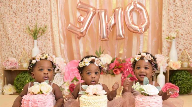 a little girl sitting at a table with a birthday cake: tolbert-triplets