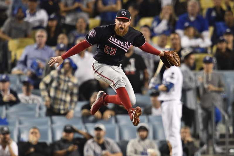 a man standing in front of a crowd of people watching a baseball game: Washington Nationals relief pitcher Sean Doolittle (63) reacts after game five of the 2019 NLDS playoff baseball series against the Los Angeles Dodgers at Dodger Stadium on October 9, 2019.
