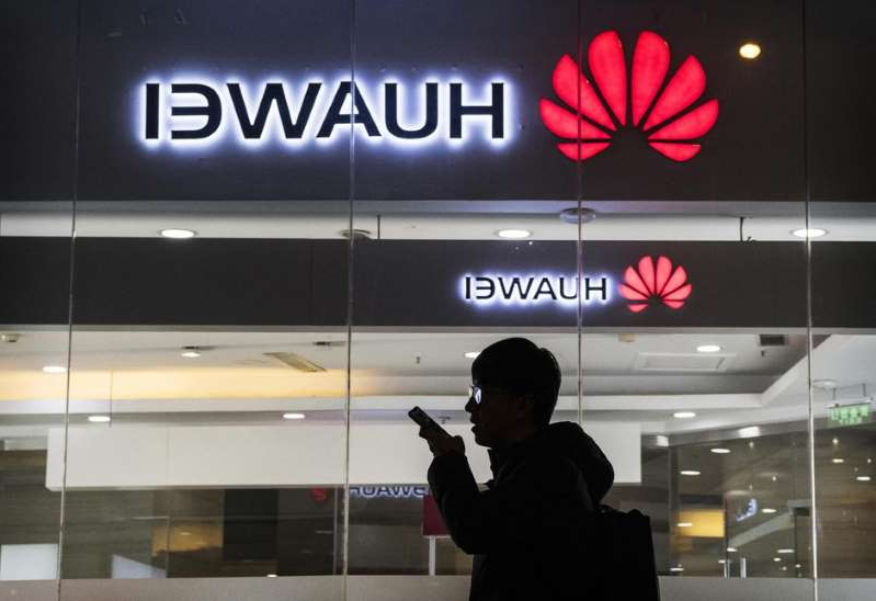 a man standing in front of a television: Huawei may soon be able to do business with some US companies again. Kevin Frayer/Getty Images