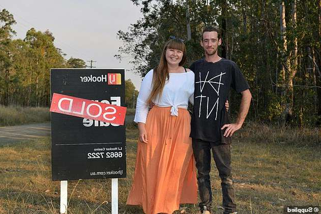 a person holding a sign posing for the camera: Hannah Lillywhite and her partner Mat Weir (pictured) had moved onto their newly purchased 13 acres of forestland in the Northern Rivers region just  three weeks ago