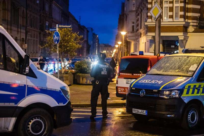 a person in a blue car parked in a parking lot: Police block a street near the shooting scene in Halle, Germany. Getty Images