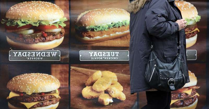 a sandwich with meat and vegetables on display in a store: An advertisement outside a fast food outlet on January 7, 2013 in Bristol, England