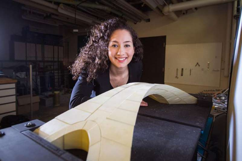 a woman smiling for the camera: MIT graduate student Karly Bast shows off a scale model of a bridge designed by Leonardo da Vinci that she and her colleagues used to prove the design's feasibility. MIT