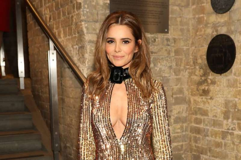 Cheryl Fernandez-Versini standing in front of a brick wall: Cheryl stunned on the red carpet of the Attitude Awards in London on Wednesday night in a sparkling gold mini dress
