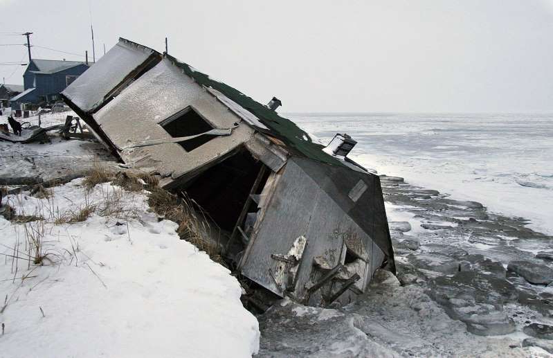 FILE - In this Dec. 8, 2006, file photo, Nathan Weyiouanna's abandoned house at the west end of Shishmaref, Alaska, sits on the beach after sliding off during a fall storm in 2005. Attorneys for 12 young Alaskans who sued over state climate change policy will argue their case before Alaska Supreme Court justices on Wednesday, Oct. 9, 2019. The lawsuit says state policy that promotes fossil fuels violates the constitutional right of young Alaskans to a safe climate. (AP Photo/Diana Haecker, File)