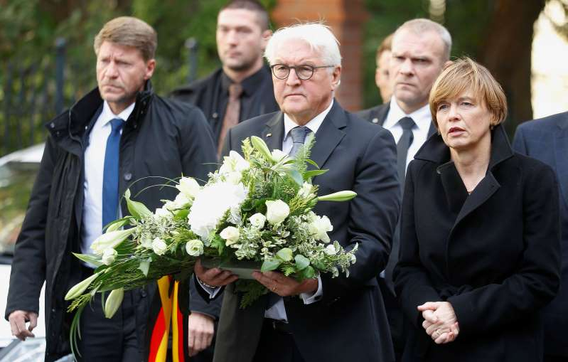 German President Frank-Walter Steinmeier holds flowers outside a synagogue in Halle, Germany October 10, 2019, after two people were killed in a shooting. REUTERS/Hannibal Hanschke