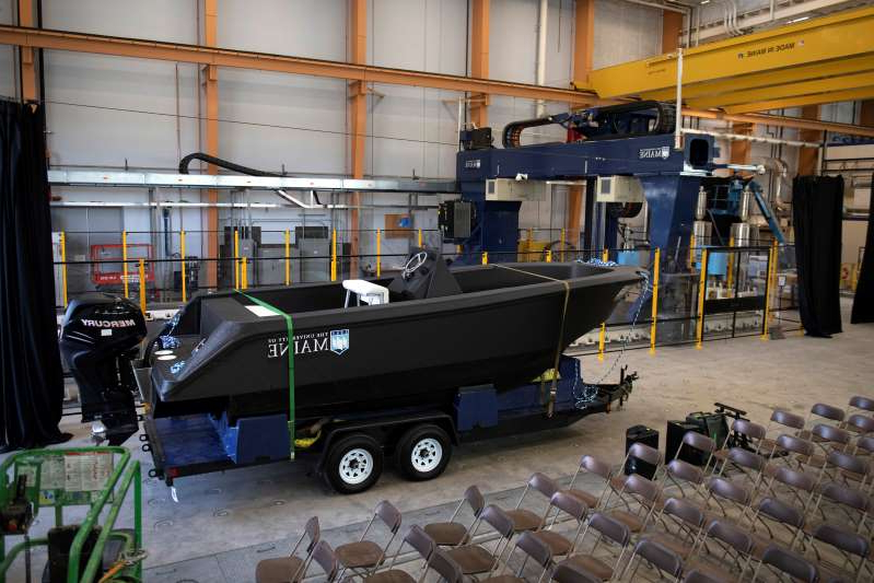 In this Wednesday, Oct. 9, 2019 photo provided by the University of Maine, a 25-foot, 5,000-pound patrol boat, center, that was produced using a large polymer 3D printer, behind left, rests on a trailer on the school's campus, in Orono, Maine. The boat was printed at the school's Composites Center on the world's largest polymer 3D printer. (Ron Lisnet/University of Maine via AP)