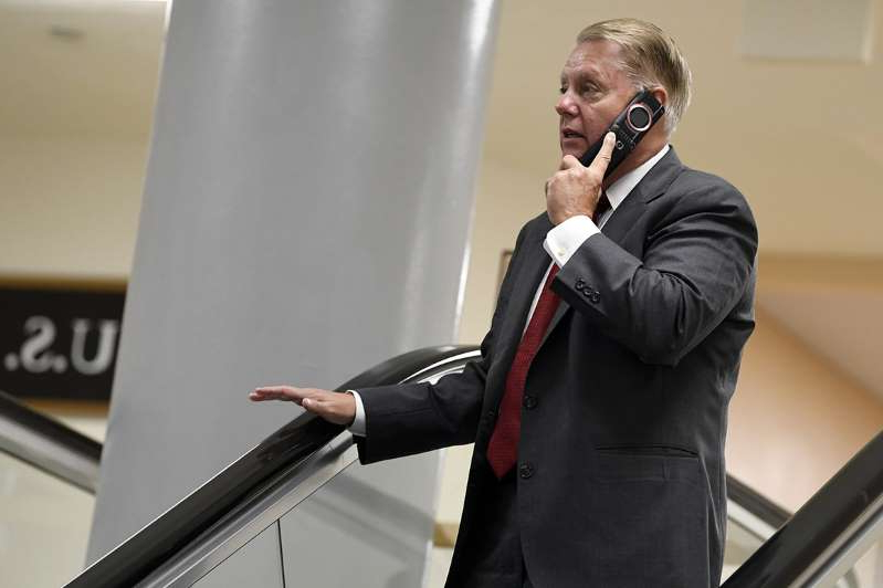 "Lindsey Graham wearing a suit and tie talking on a cell phone: Sen. Lindsey Graham labeled the Kurds a ""threat"" in a phone call with a couple pranksters posing as Turkey's minister of defense."