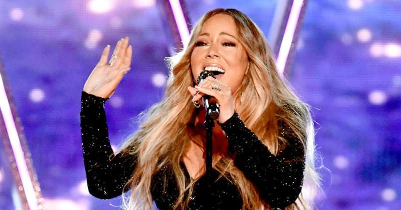Mariah Carey talking on a cell phone on a stage: Mariah Carey to detail the 'debacle' that was 'Glitter' in new memoir