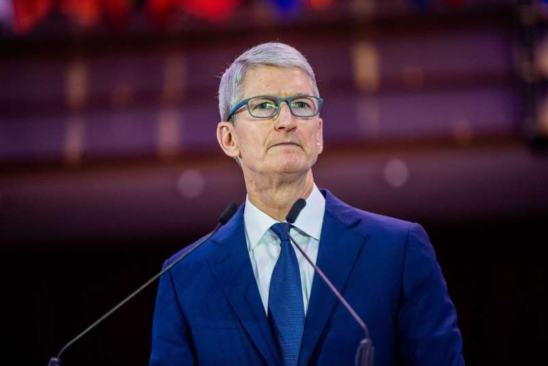 Tim Cook wearing a suit and tie: tim-cook-apple-sign