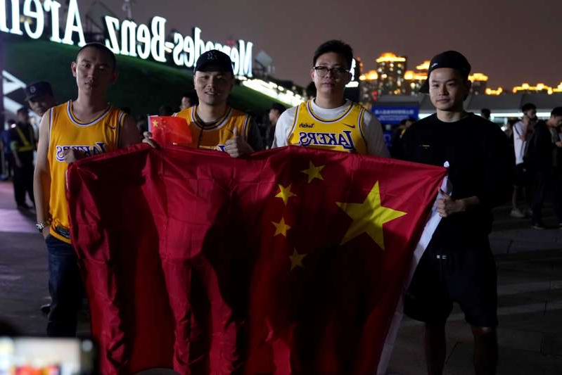 a group of people holding a sign: Fans in Los Angeles Lakers jerseys hold Chinese national flags as they pose for pictures outside the Mercedes-Benz Arena before the NBA exhibition game between Brooklyn Nets and Los Angeles Lakers in Shanghai