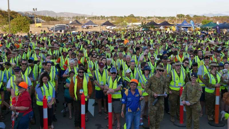 a group of people standing in front of a crowd posing for the camera: Thousands turned up to the Idalia carpark to break the world record. (ABC North QLD: Hannah Palmer)