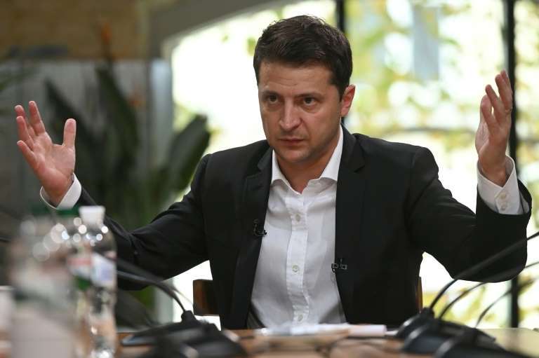 a person holding a glass of wine: Zelensky's achievement has yet to be verified by an international body