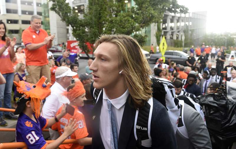a person standing in front of a crowd: Clemson quarterback Trevor Lawrence walks past the crowd on Sept. 14, 2019.
