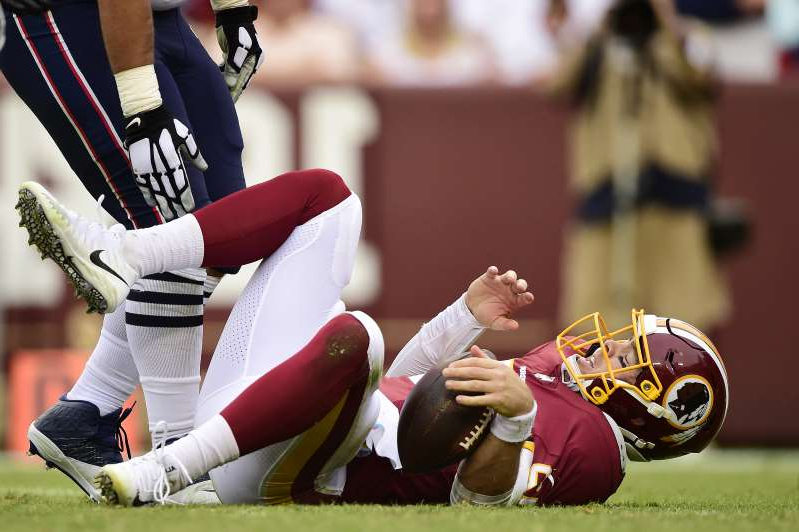a woman with a baseball glove: Colt McCoy of the Washington Redskins reacts after being sacked by the New England Patriots. (Getty Images)