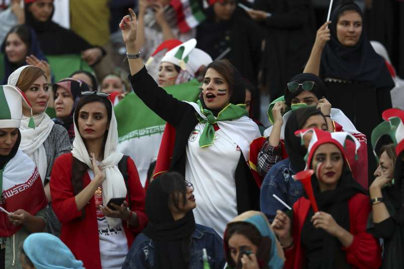 Iranian nurse Zahra Pashaei, center, cheers during an Iran and Cambodia 2022 World Cup qualifier soccer match at the Azadi (Freedom) Stadium, in Tehran, Iran, Thursday, Oct. 10, 2019 Iranian women were freely allowed into the stadium for the first time in decades. The decision follows the death of a young woman who set herself on fire after hearing she could face prison time for sneaking into an Iranian soccer match disguised as a man. (AP Photo/Vahid Salemi)