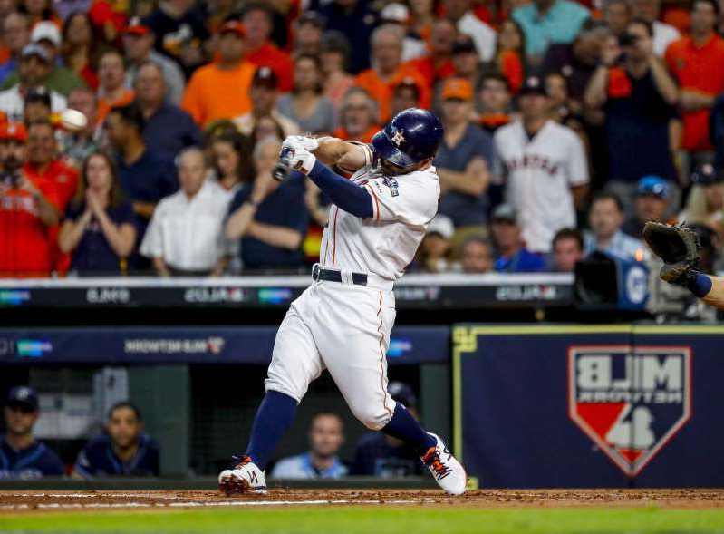 a baseball player holding a bat in front of a crowd: Houston Astros second baseman Jose Altuve (27) hits an RBI single to drive home George Springer during the first inning of Game 5 of the American League Division Series at Minute Maid Park in Houston, on Thursday, Oct. 10, 2019.